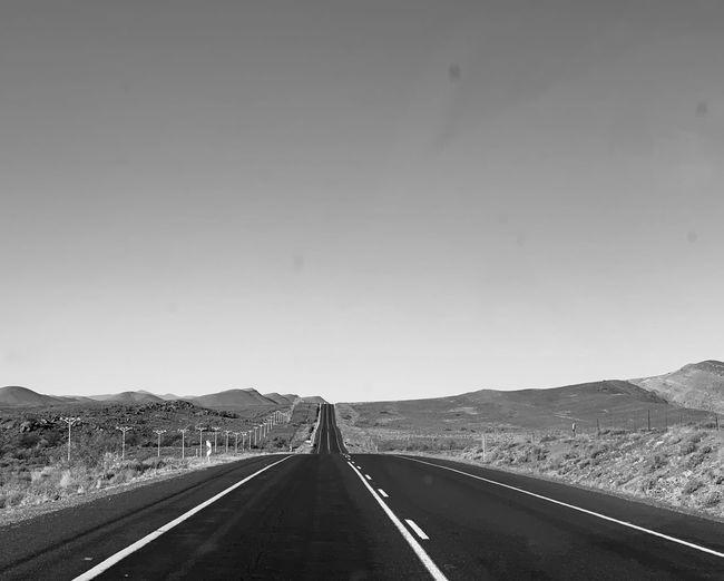 Road leading towards mountain against sky