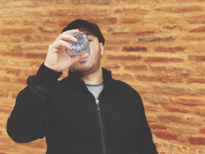 Man drinking water from bottle against brick wall