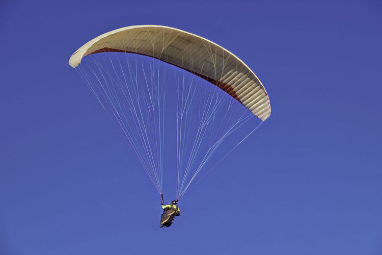 Low angle view of person paragliding against clear blue sky on sunny day