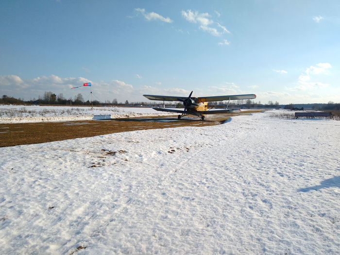 Airplane on snowy land against sky during winter
