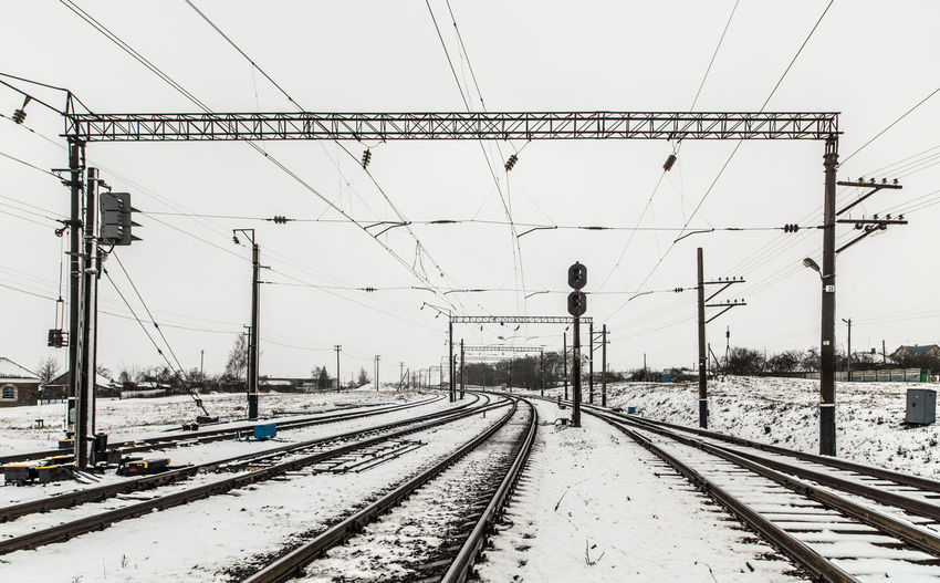 Railroad tracks by snowcapped mountain against sky