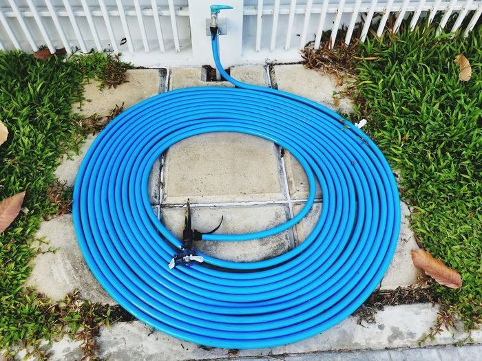 High angle view of water pipes rolled up on footpath in yard