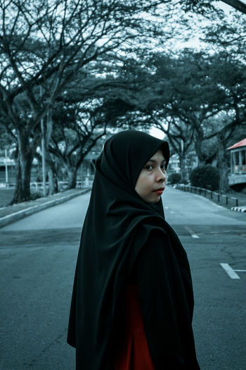 Portrait of woman standing by road against trees