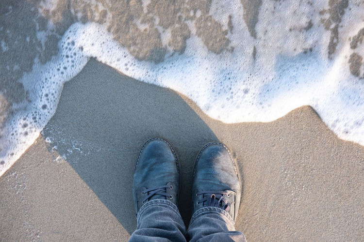Low Section Human Leg One Person Jeans Human Body Part Personal Perspective Body Part Real People Water Beach Lifestyles Land High Angle View Shoe Leisure Activity Casual Clothing Nature Standing Outdoors Human Foot Human Limb