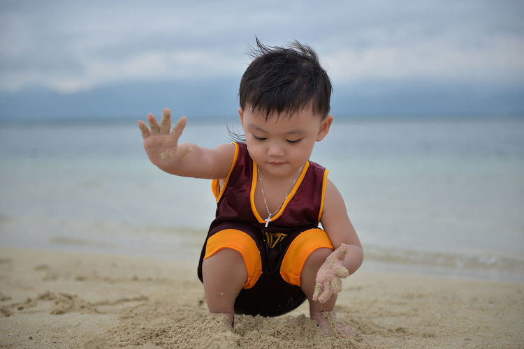 Beach Boy Child Childhood Children Only Day Eyeem Philippines Front View Full Length Fun Happiness Looking Down Males  Nature One Person Outdoors People Playing Sand Sand Pail And Shovel Sea Sky Smiling Vacations The Portraitist - 2017 EyeEm Awards Live For The Story