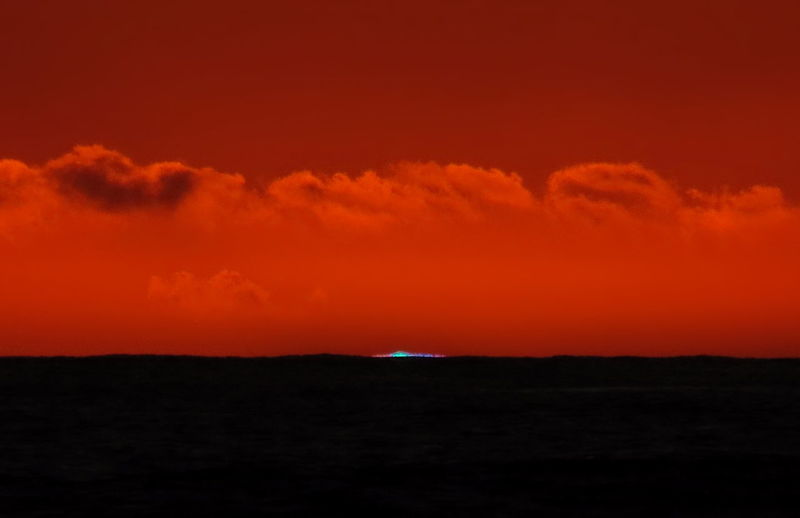 A colorful green flash over the ocean at the very end of a beautiful sunset. Atmosphere Green Green Flash Orange Pacific Skies Spectrum Astronomicalclock Astronomy Atmospheric Blue Clouds Colorful Dramatic Dusk Flash Horizon Mirage Ocean Phenomena Phenomenon Red Refraction Sky Sunset