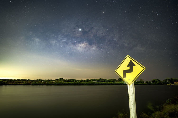Signs, signs, beware of curves at night, behind the sign, with the Milky Way. Scenics - Nature Star - Space Sky Space Beauty In Nature Astronomy Night Tranquil Scene Tranquility Nature No People Water Sign Communication Star Lake Road Outdoors Guidance