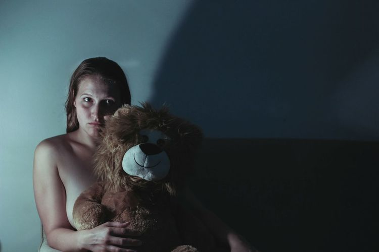 Portrait Of Naked Woman Holding Teddy Bear While Sitting Darkroom