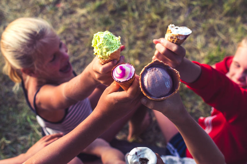 High Angle View Of Smiling Siblings Toasting Ice Creams