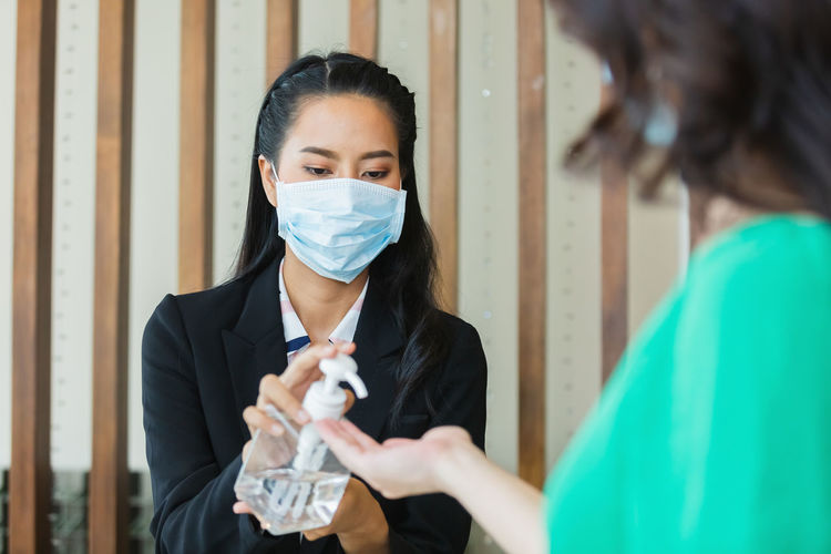 Woman hotel receptionist wearing medical mask squeeze alcohol gel sanitizer hand cleanning.