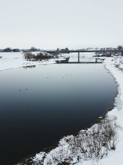 Water Lake Nature Reflection Outdoors Floating On Water Sky Beauty In Nature Tranquility Scenics Day Refraction Extreme Weather No People Winter Wintertime Cold White Blue Grey Landscape Bridge Small Town Russia