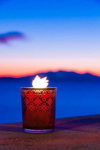 Close-up of illuminated tea light against sky during sunset