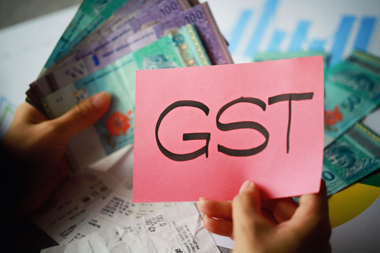 Cropped image of woman holding currency with gst text on paper
