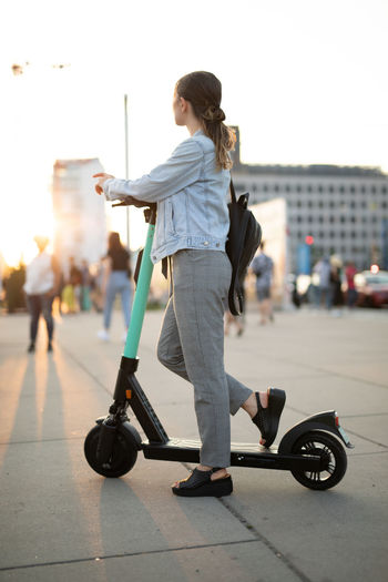 Woman riding push scooter on street against clear sky in city