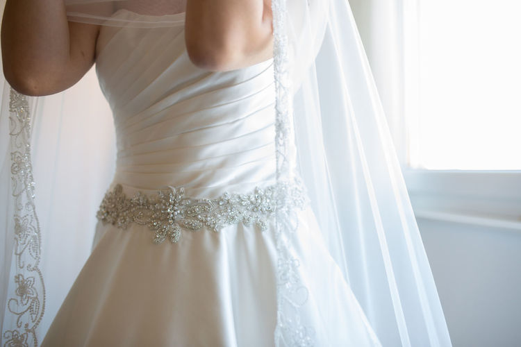 Midsection of bride standing by window