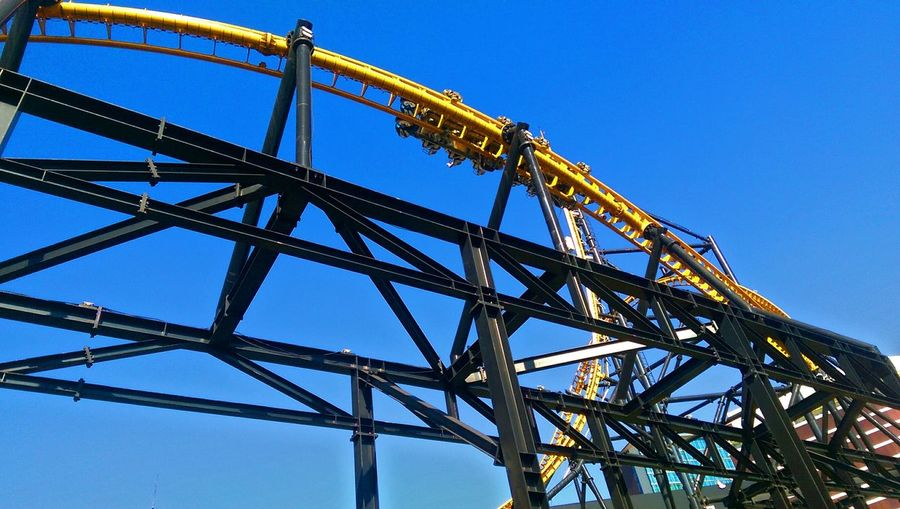 Low Angle View Of Roller Coaster Against Blue Sky