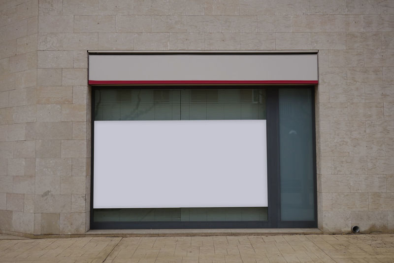 Blank billboard in a glass showcase Advertising Office Advertisement Architecture Billboard Blank Building Building Exterior Built Structure Copy Space Day Door Empty Entrance Flooring Glass Glass - Material Mock Up No People Outdoors Rectangle Wall Wall - Building Feature White Color Wood - Material