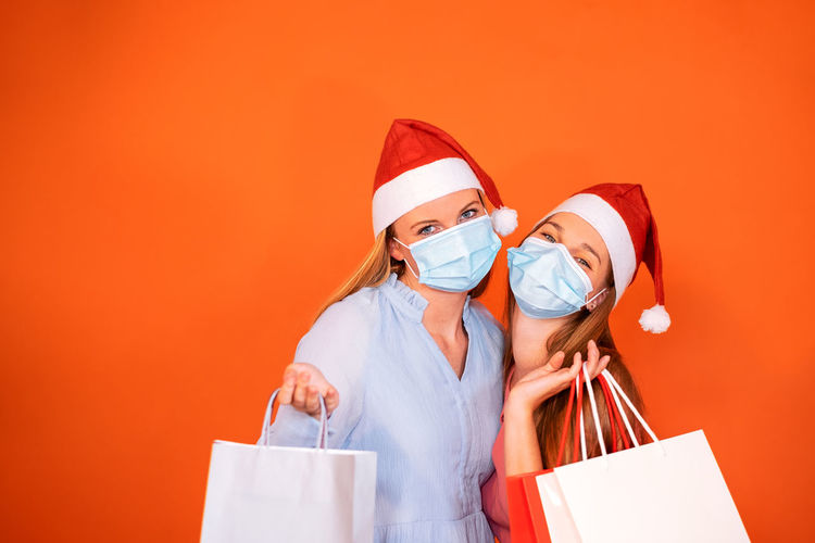 Two girls wearing a christmas hat and medical mask holding colored shopping paper bags
