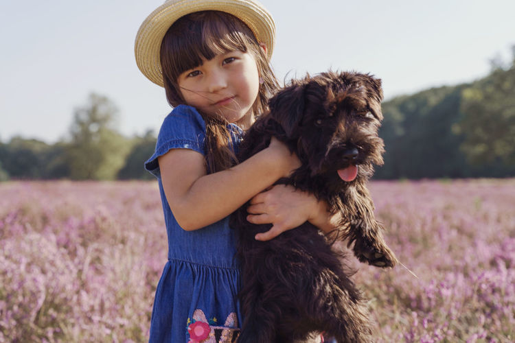 Full length of girl with dog on field