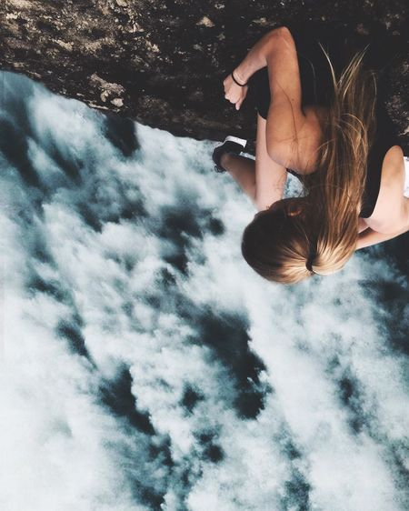 Upside down image of woman sitting on rock formation against cloudy sky
