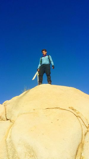 Low angle view of man holding knife while standing on rock against clear blue sky