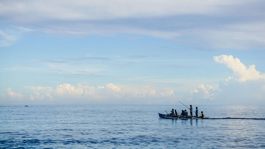 Traveling at sea Calm Sea Calm Water Horizon Over Water Motor Boat Silhouette Clouds Shadow Boat Water Rowing Sea Blue Sunset Teamwork Sky Rowboat Fisherman Fishing Boat