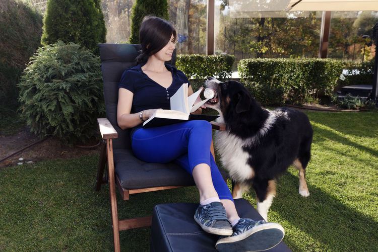 Full length of woman holding book while sitting by dog