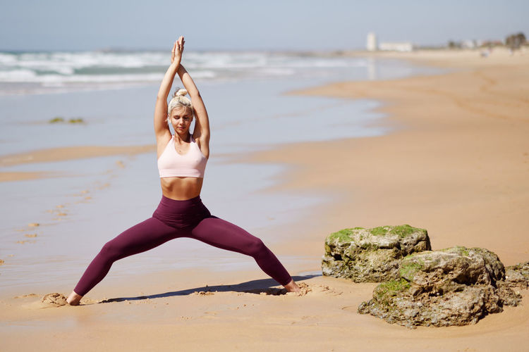 Caucasian woman practicing yoga at seashore. Young female raising arms in the beach in Cadiz, Andalusia, Spain. Beach Land Full Length One Person Young Women Water Sea Lifestyles Wellbeing Exercising Healthy Lifestyle Sand Relaxation Exercise Leisure Activity Yoga Real People Young Adult Human Arm Arms Raised Yoga