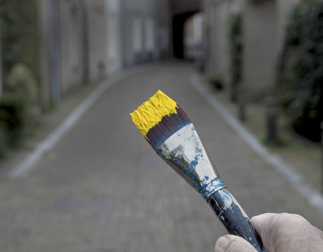 Close-up of hand holding umbrella on road