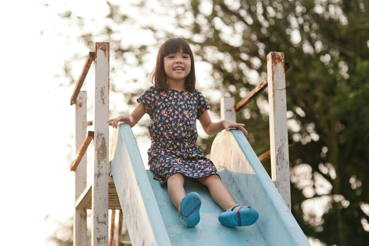 Portrait of girl sliding down on slide in park