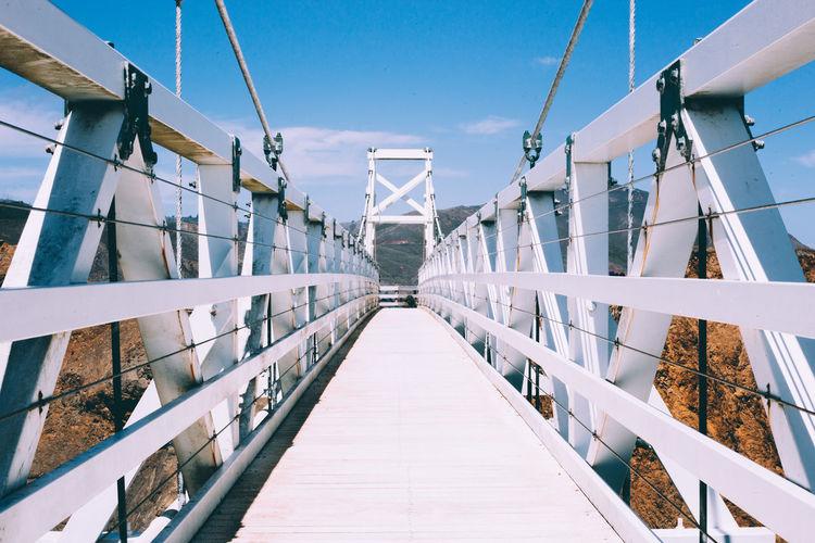 View of footbridge against blue sky