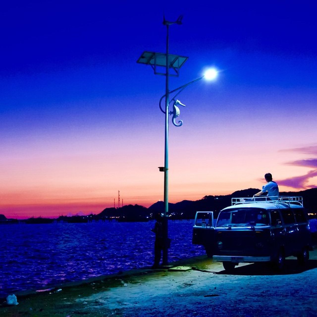 sunset, transportation, mode of transport, car, silhouette, sky, land vehicle, street light, nature, illuminated, outdoors, sea, real people, water, beauty in nature, clear sky, blue, day
