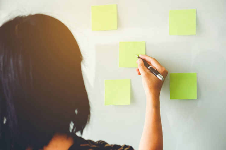 Rear view of woman writing on green adhesive notes on whiteboard