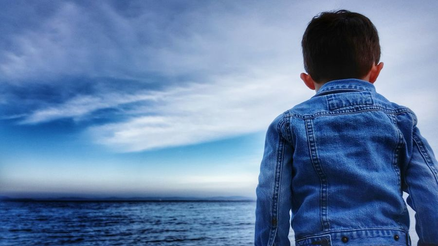 Rear view of a boy overlooking calm blue sea