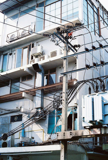 Cables in front of building exterior Architecture Architecture Bangkok Building Exterior Built Structure Cable City Color Palette Colors Day Film Filmisnotdead Filmphotography Low Angle View Outdoors Technology Urban Urban Design Urban Landscape