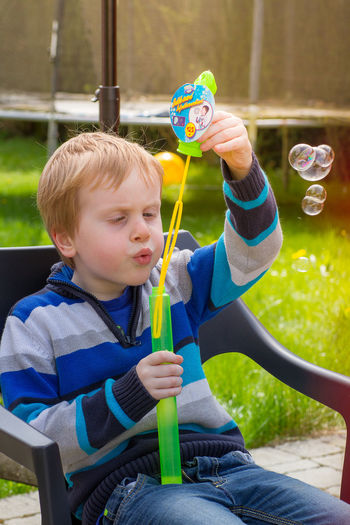 Boy blowing bubbles while sitting in yard