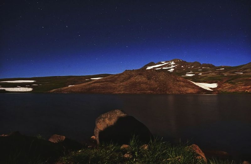 Scenic view of lake by mountain against sky at night
