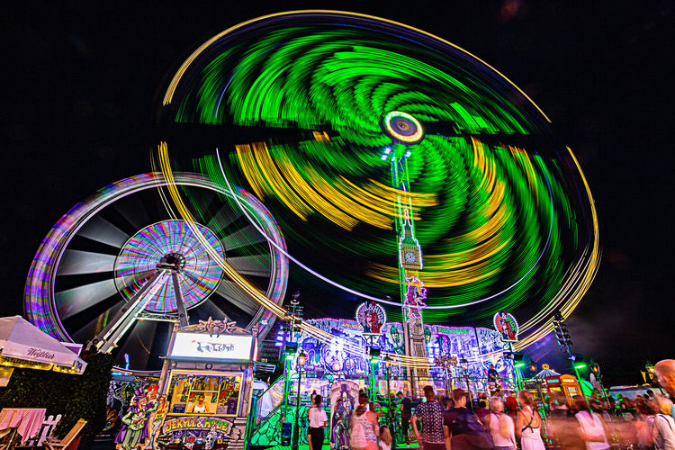 Amusement Park Amusement Park Ride Arts Culture And Entertainment Blurred Motion Carnival Crowd Enjoyment Excitement Fairground Ferris Wheel Festival Group Of People Illuminated Large Group Of People Leisure Activity Long Exposure Motion Multi Colored Night Nightlife Outdoors Real People Sky Speed Spinning