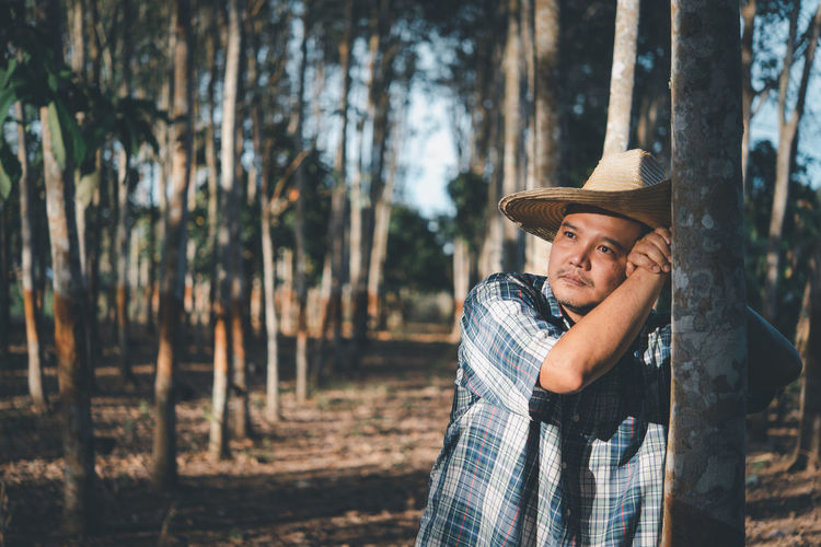 Mid adult man wearing hat on tree trunk in forest