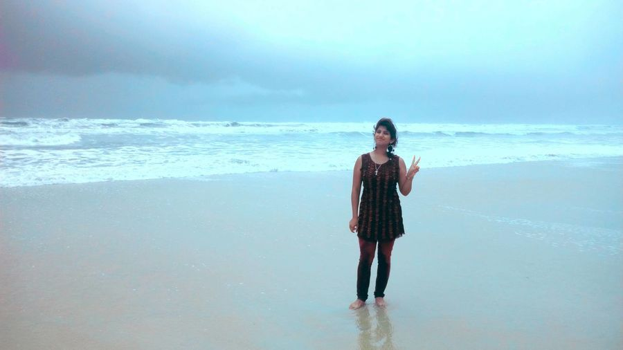 Portrait of young woman showing peace sign while standing at beach against cloudy sky