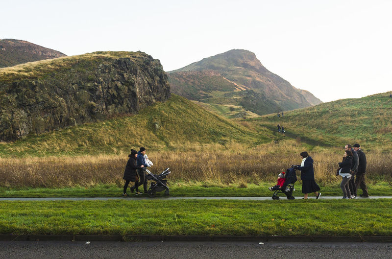 Rear view of people riding motorcycle on mountain against sky