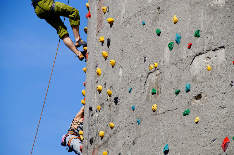 Low angle view of people climbing wall