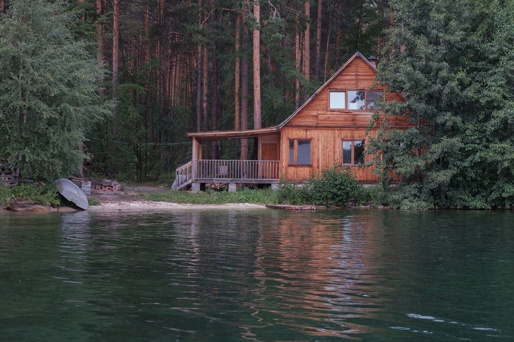 House by lake and trees in forest