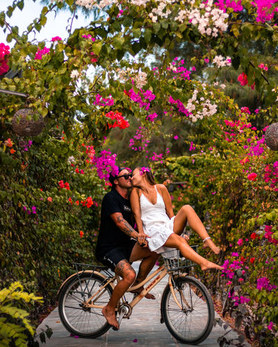 Romantic couple riding a bicycle surrounded by flowers