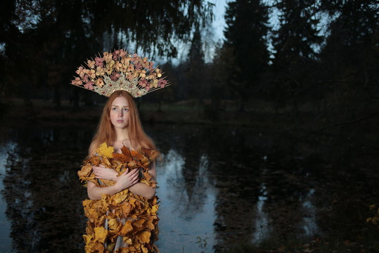 Young woman looking away while wearing headdress by lake in forest
