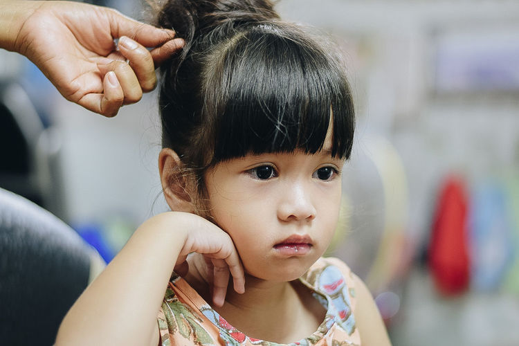 Cropped hand hairstyling girl