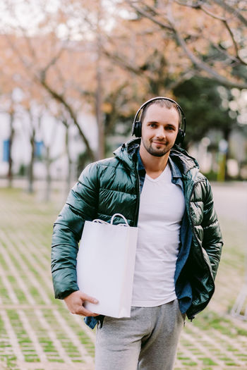 Portrait of mid adult man holding bag while standing outdoors
