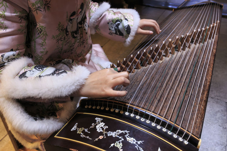 Close up of hands of a Chinese woman playing a zither, a traditional Chinese musical instrumenta Zither Close-up China Sichuan Music Chinese Tradition Folk Instrument Stringed Instrument
