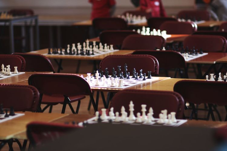 Chess on table amidst chairs