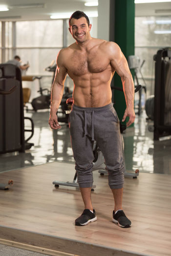 Portrait of happy shirtless man standing in gym